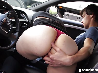Old tolerant sucks young cock in the car and gets her pussy licked in public